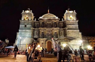 Night shot of a white limestone Cathedral in Oaxaca Mexico with bicycle carts in front of it.