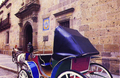 A colorful horse-drawn carriage outside of a stone building on a cobble stone street in Juan Diego, Mexico.