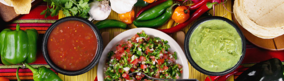 Colorful salsa, guacamole, and peppers