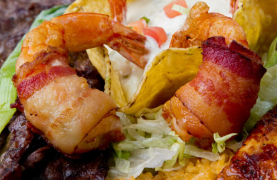 Shrimp wrapped in bacon on a tortilla shell with shredded lettuce.