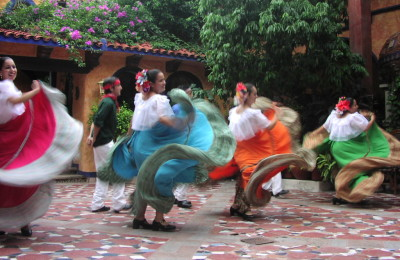 Four Mexican women dancing with colorful skirts.