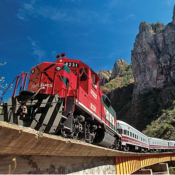 A red and green train crossing a bridge in the mountains of Mexico