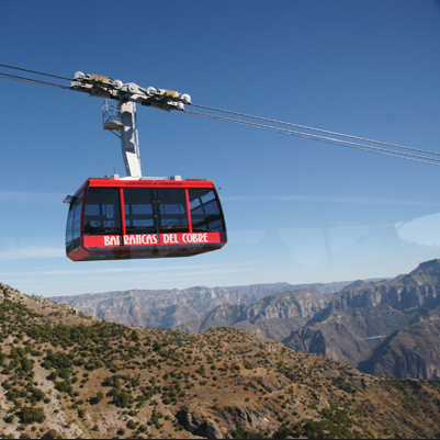 A red Copper Canyon Tram traveling up the mountain.