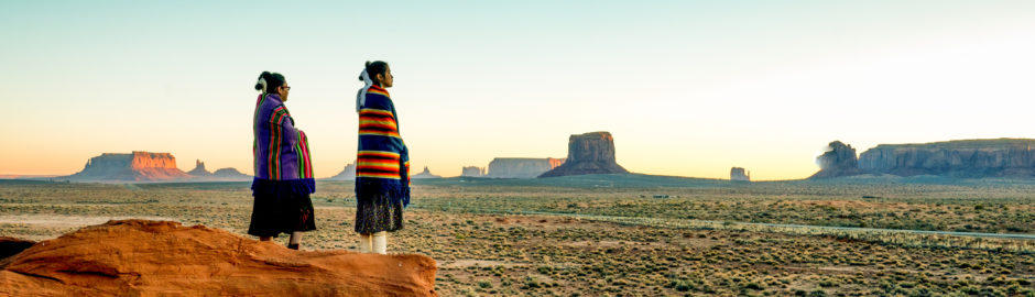 Navajo girls wrapped in handwoven traditional blankets enjoying a grand sunset in Monument Valley